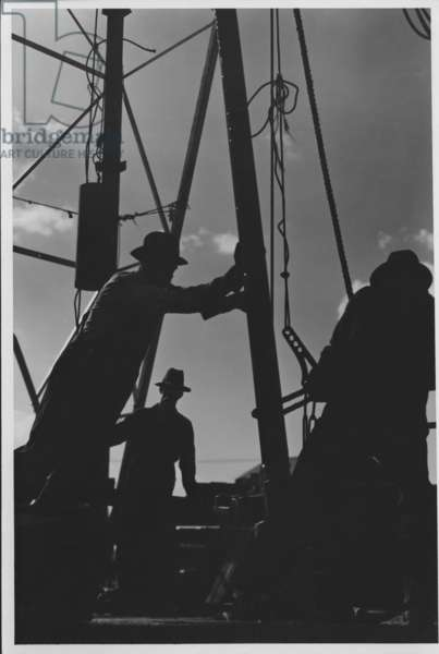 Silhouetted Workmen on Oil Derrick, Texas, 1935-36 (b/w photo)