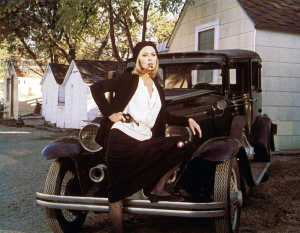 Full Shot Of Faye Dunaway As Bonnie Parker Leaning On Car While Holding A Gun/Pistol, Cigarette In Mouth.