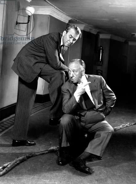 Director Alfred Hitchcock (1899 - 1980) posing with actor James Stewart (1908 - 1997), who starred in several of his films (b/w photo)