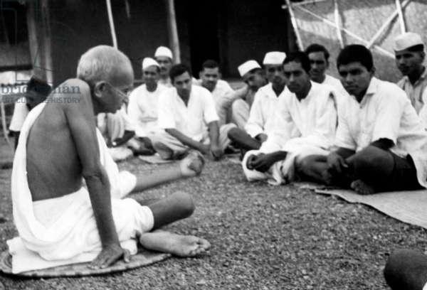 Mahatma Gandhi speaking to Harijan workers, Sevagram Ashram, September 1940 (b/w photo)