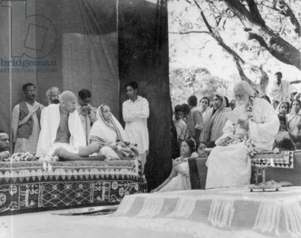 Poet Rabindranath Tagore delivering an address of welcome to Mahatma Gandhi and his wife Kasturba, February, 1940 (b/w photo)