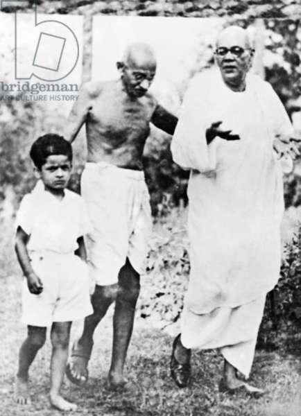 Mahatma Gandhi walking with a boy and Sarat Chandra Bose, 1945 (b/w photo)