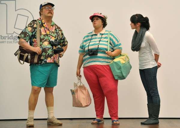 """A woman (R) observes Figures II """"Tourists"""", by Duane Hanson, at the exhibition Duane Hanson - Gregory Crewdson, Uncanny Realities, Baden Baden, 2010"""