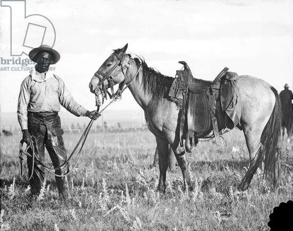 Black cowboy and horse, c.1890-1920 (b/w photo)