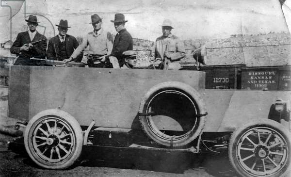 Men with rifles and artillery in an armoured vehicle, 1913 or 1914 (b/w photo)
