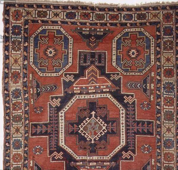 Kazak rug, with central cruciform medallion and a border of stylised flowerheads, Persian (detail)