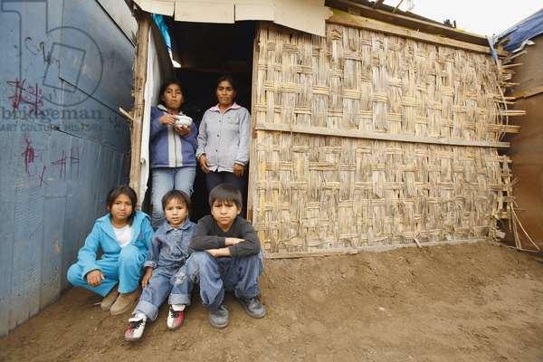Family Members At Entrance to Slum Dwelling, Lima, Peru (photo)