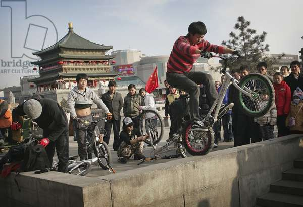 Chinese Youths Riding Mountain Bikes Near An Ancient Bell Tower, Xian, Xi'an, Capital of Shaanxi Province, China (photo)