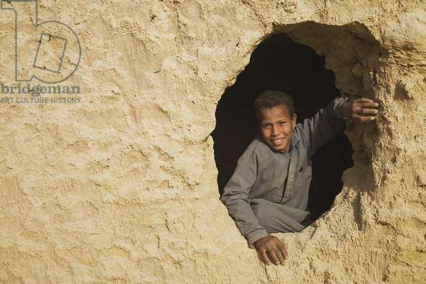 A Smiling Berber Boy looking out from the Fortress of Shali in Siwa, Egypt (photo)