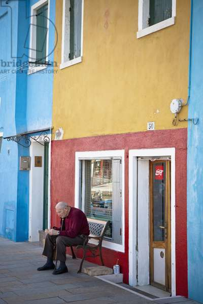 A Man sitting  on a Bench outside a Shop, Burano Venezia Italy (photo)