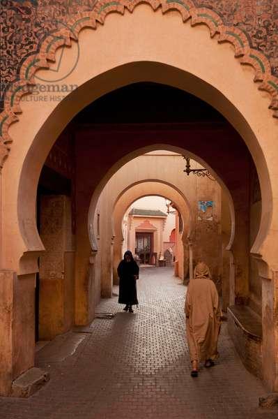 Morocco, Men walking through arched alleyway in Medina of Marrakesh, Marrakesh (photo)