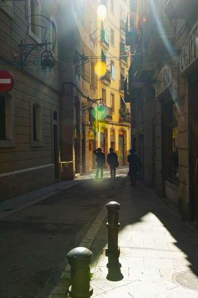Pedestrians on a narrow walkway between buildings, Barcelona, Spain (photo)
