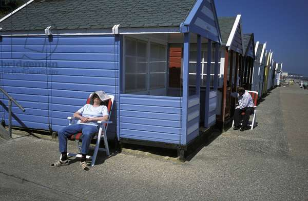 Woman Sleeping with Newspaper on Head Outside Beach Hut, Southwold, Norfolk, UK (photo)