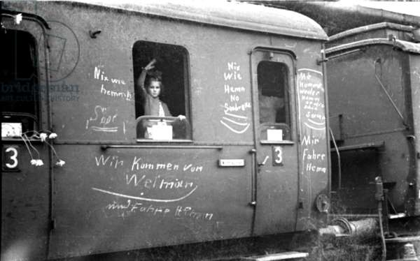 Girl waving from train with Nazi graffiti.