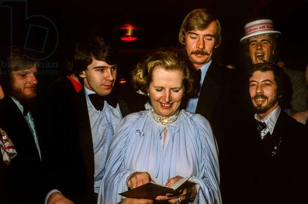 Margaret Thatcher accompanied by protection detectives signing autographs at the Conservative Party Conference Ball, 1979 (photo)
