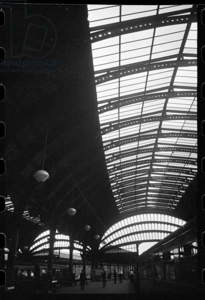 An interior view of York Railway Station, showing platforms extending out from under the building, wrought-iron roof trusses and trains and passengers on the platforms, c.1955-c.1980 (b/w photo)