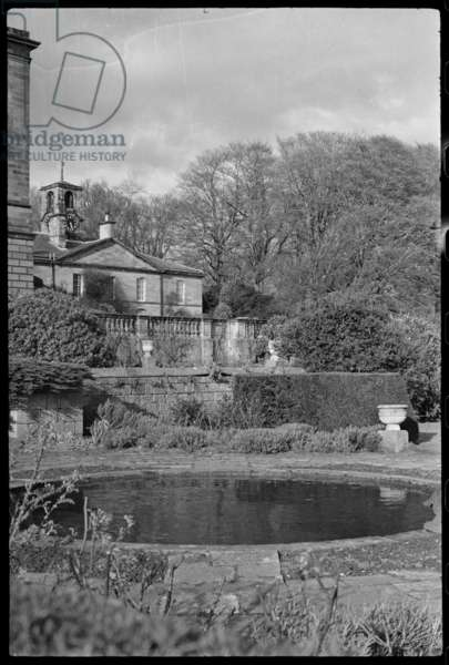 The south elevation of the main stableyard block at Howick Hall, seen from the garden of the main house, with a circular pond and stepped terrace in the foreground, c.1955-c.1980 (b/w photo)