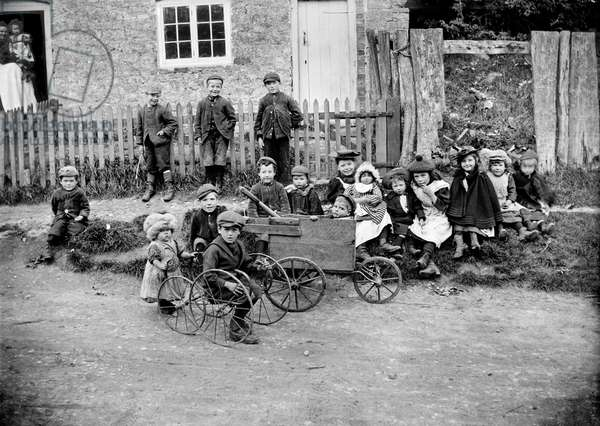 General view of a group of children gathered outside a house (b/w photo)