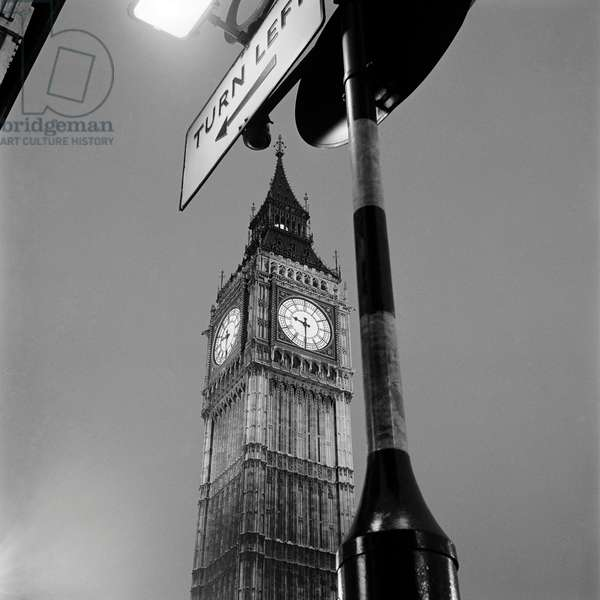 Palace of Westminster, London: the Clock Tower colloquially known as Big Ben, view looking up from ground level with a street sign framing the tower in the foreground, 1965 (b/w photo)