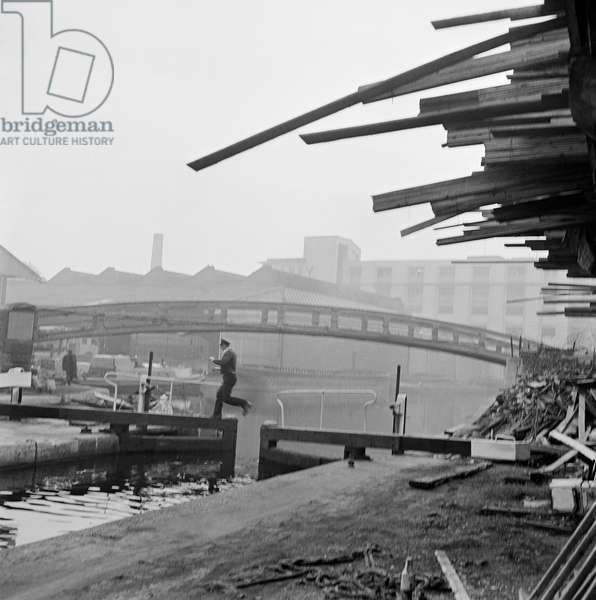 Hampstead Road Canal Lock, Regents Canal, Camden Town, London: a uniformed man jumping from one opening lock gate to the other, a roving bridge in the midground and canal warehouses beyond, 1955-65 (b/w photo)