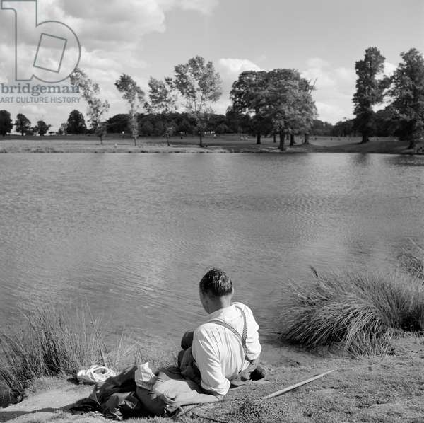 Richmond Park, London: a man in shirt sleeves and braces relaxing by the side of a lake with fishing rod and net beside him, 1962-64 (b/w photo)