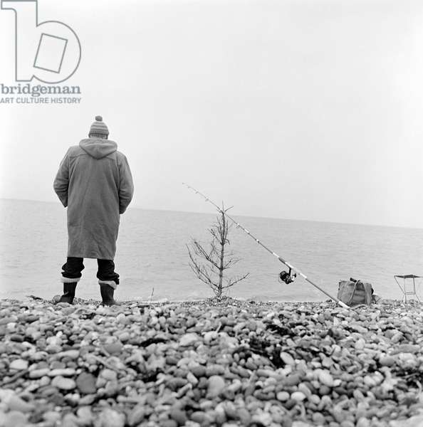 A man fishing on a shingle beach in Kent, with his fishing rod propped on a bare Christmas tree, 1965-72 (b/w photo)