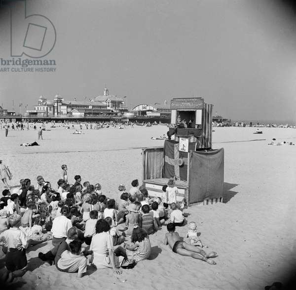 Children watching a Punch and Judy show on the beach with the Britannia Pier in the background, 1948 (b/w photo)