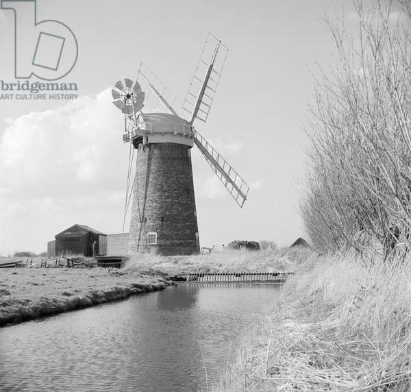 View looking down the watercourse towards Horsey Drainage Mill, Horsey Straithe, Norfolk, 1963 (b/w photo)