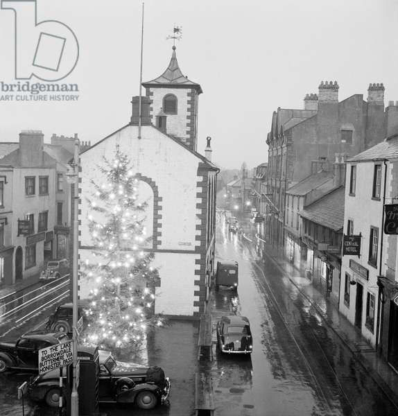 Moot Hall, Main Street, Keswick, Cumbria: showing a large illuminated Christmas tree in the market square, with vehicles leaving trails of light in the dark and wet winter conditions, between 22nd December 1953 and 7th January 1954 (b/w photo)