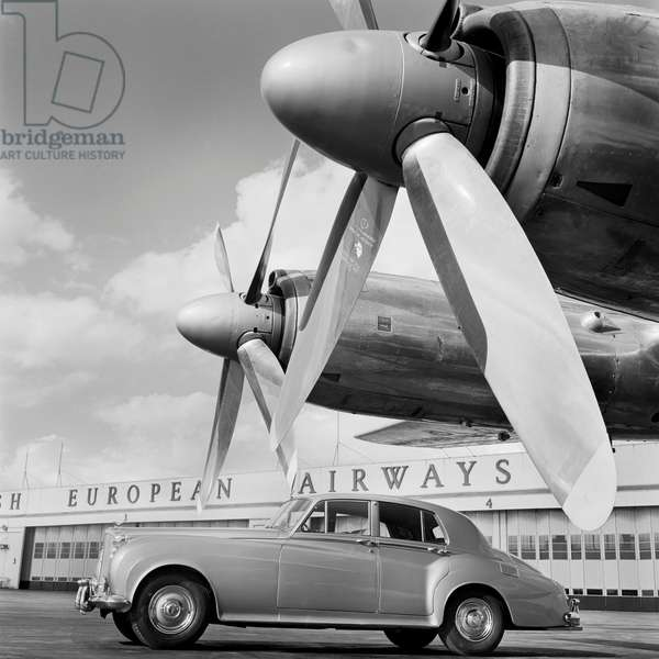Heathrow airport, B E A Aircraft Hangar, London: a Bentley car parked on the runway in front of the British European Airways buildings, 1960-74 (b/w photo)