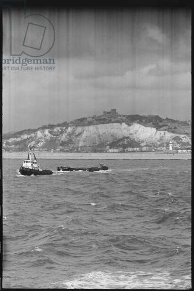 A view of Dover Castle, seen from the south, with the Outer Harbour wall and two boats in the foreground, and a view of the white cliffs and castle in the background, Dover Castle, Dover, Kent, UK, c.1955-80 (b/w photo)