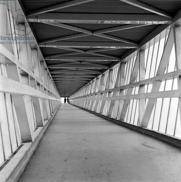 London docks: interior of covered footbridge at the docks with a couple of women walking at the far end, 1965 (b/w photo)
