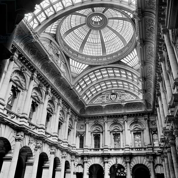 Royal Exchange, City of London: interior view of the elaborate vaulted and domed cast iron and glass roof and pedimented Ionic first floor windows, 1960-75 (b/w photo)