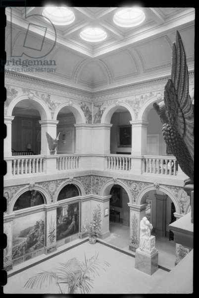 An interior view of Wallington Hall, showing the Central Hall, which is arcaded on all sides and has Pre-Raphaelite murals on the walls and a number of statues, seen from the second floor of the hall, Wallington Hall, Wallington Demesne, Northumberland, UK, c.1968-80 (b/w photo)