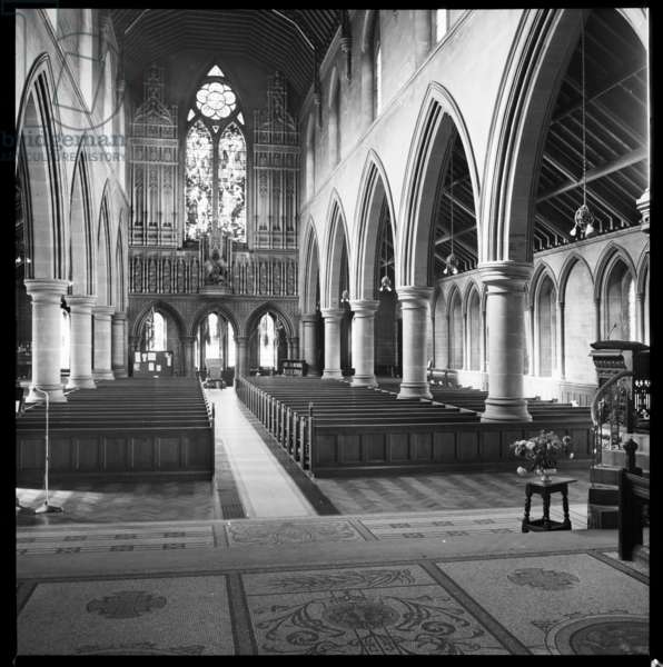 An interior view of the chancel in St George's Church, showing the nave and west wall, traceried with Caen stone and with a statue of St George, c.1955-c.1980 (b/w photo)