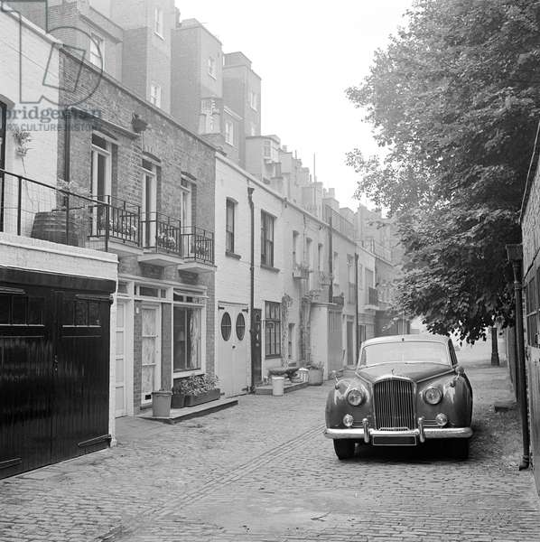 Minera Mews, Belgravia, Westminster, London: a Rolls Royce parked on the road opposite the houses, 1962-64 (b/w photo)