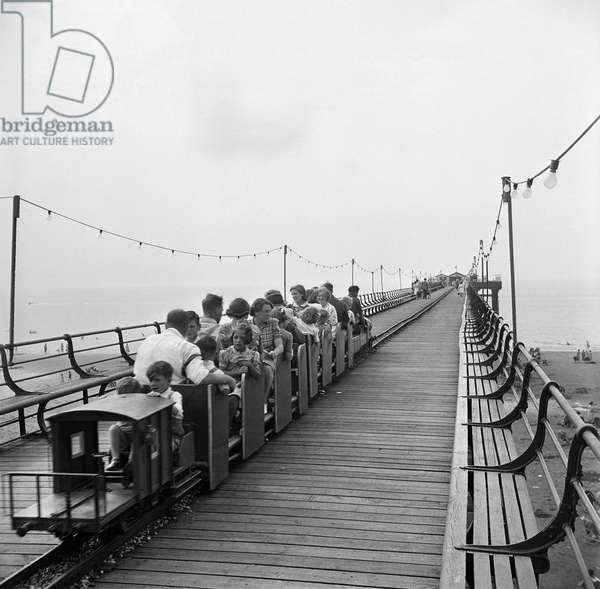 General view showing a train running along a miniature railway on Hunstanton Pier, 1940-59 (b/w photo)