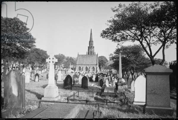 An exterior view of the chapels in St John's Cemetery from the west, with the roof of the Mather Tomb on the far right side, and headstones and monuments in the foreground, c.1955-c.1980 (b/w photo)