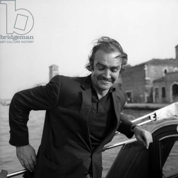 Scottish actor Sean Connery, wearing a blazer and a polo shirt, portrayed on a water taxi, looking down, his hair in a mess, in the venetian lagoon, Venice 1970s