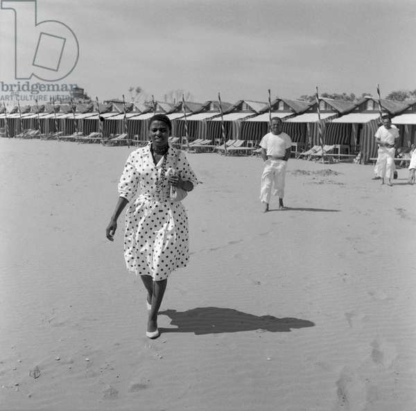 South african singer and civil rights activist Miriam Makeba, wearing a polka-dotted dress and holding a handbag, portrayed while walking on the Lido beach, Venice 1959 ©Archivio Cameraphoto/leemage