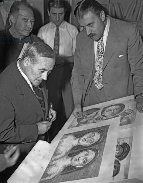 Spanish painter Joan Miro', wearing a suit and a striped tie, portrayed while looking at Campigli drawings, the art promoter Carlo Cardazzo next to him, Venice, 1958 (b/w photo)