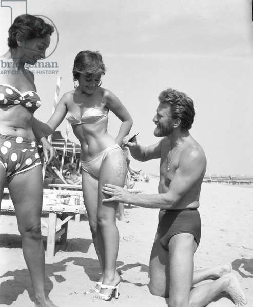 American actor Kirk Douglas, wearing a swimming suit and a necklace chainlet, signing on the thigh of the paintress Novella Parigini, wearing a strapless bikini and round earrings, a woman wearing a strapless polka-dotted bikini, Lido Beach, Venice 1953