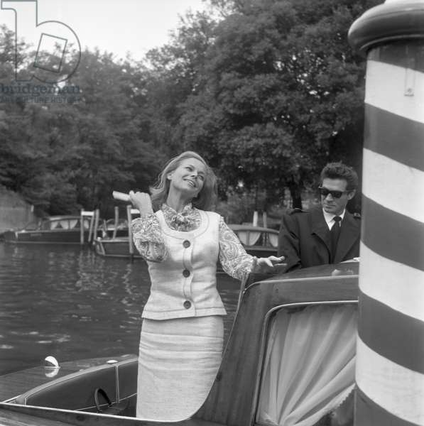 English actress Honor Blackman brushing her hair with Maurice Kaufmann on a water taxi, Lido, Venice, 1965 : Brushing Her Hair