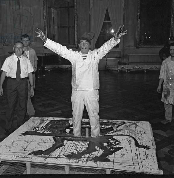 Spanish painter Salvador Dali, wearing a striped T-shirt, a hat and an overalls, portrayed while standing on one of his painted canevas depicting the venetian lion during a performance, Venice, 1961