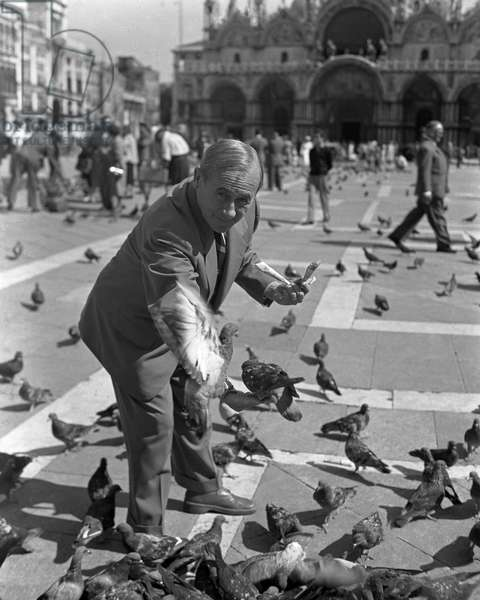 Spanish painter Joan Miro, wearing a suit and a striped tie, portrayed in St. Mark Square while feeding pigeons, Venice 1948