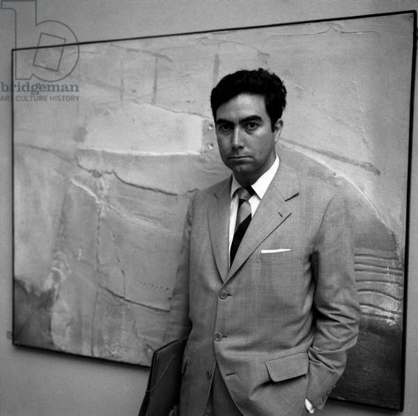 Spanish painter Antonio Tapies, wearing a suit and holding a folder, presents his paintings atthe Art Biennalein Venice, 1958