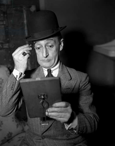 Italian actor Toto', Antonio De Curtis, wearing a blazer, a tie a ring and a bowler hat, portayed while painting his eyebrows with a pencil and looking at himself in a mirror, 1950
