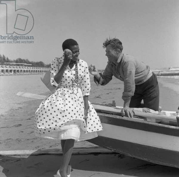 South african singer and civil rights activist Miriam Makeba, wearing a polka-dotted dress and holding a handbag, portrayed while sitting on a boat and listening to the sea sound in a shell, a man smiling to her, Lido beach, Venice 1959 ©Archivio Cameraphoto/leemage