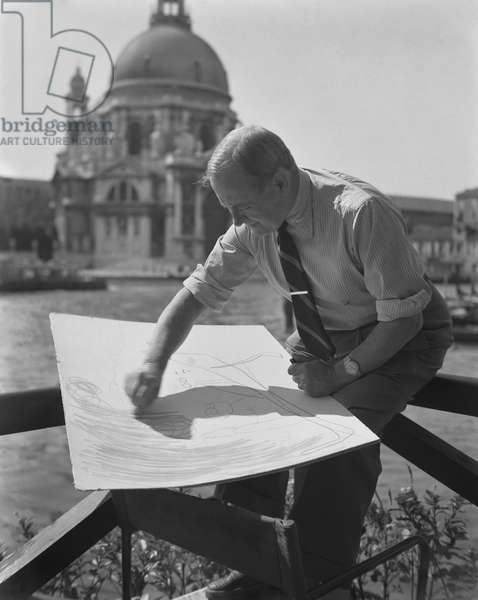 Spanish catalan painter Joan Miro, wearing a striped ciphered shirt, a striped tie and a watch, sitting on a fence in front of la Salute church, drawing on a big paper with a pencil, Venice, 1952 (b/w photo)
