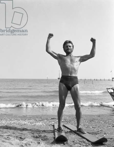 American actor Kirk Douglas, wearing a swimming suit and a necklace chainlet, portrayed while wearing a pair of waterski, on the Lido beach, Venice 1953